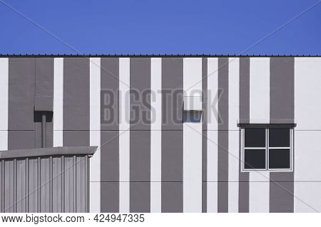 Glass Window With Air Vent On Modern White And Grey Building Against Blue Sky Background