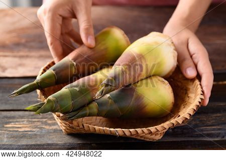 Fresh Bamboo Shoot In A Basket With Hand On Wooden Background, Edible Vegetable In Asian Cuisine