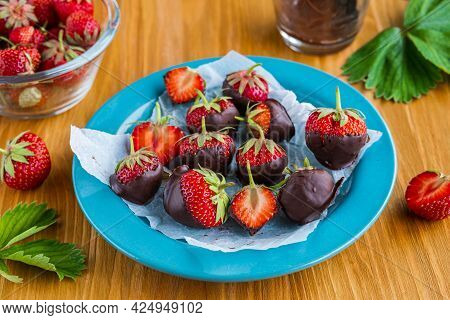 Dessert, Fresh Strawberries Covered With Dark Chocolate, On A Blue Plate On A Brown Wooden Backgroun