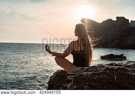 Young Woman With Long Hair In Black Swimsuit And Boho Style Braclets Practicing Outdoors On Yoga Mat