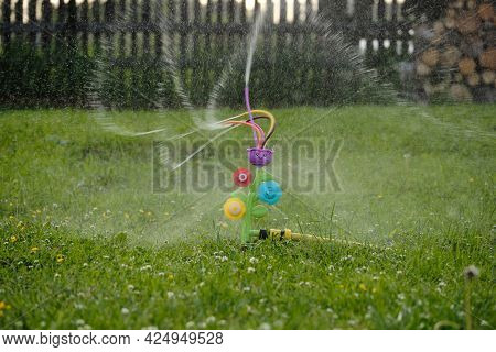 Plastic Toy Nozzle In The Shape Of A Flower For Watering The Lawn. Splashes Of Water Scatter In Diff