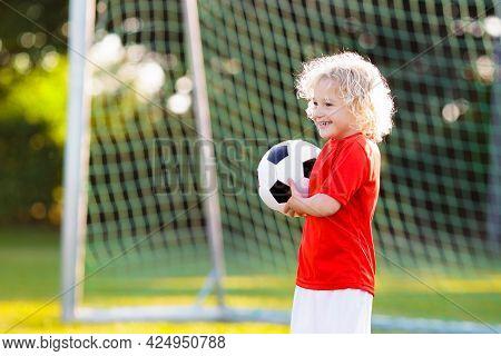 Kids Play Football On Outdoor Field. Children Score A Goal At Soccer Game. Little Boy Kicking Ball.