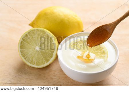 Fresh Lemon And Yogurt In A Bowl With Spoon Pouring Honey, Healthy Eating And Beauty Skin Care