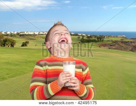 Happy child drinking milk in a beautiful landscape