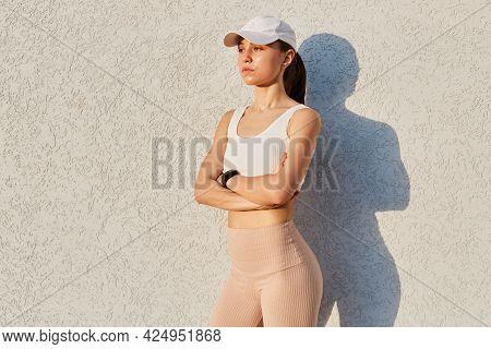 Outdoor Shot Of Confident Girl Wearing Visor Cap, White Top And Beige Leggins, Folded Hands, Having