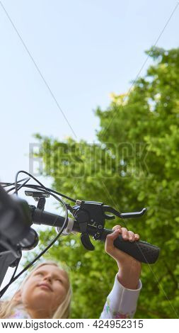 Focus On Hand On The Bicycle Handlebar. Young Girl In A Bicycle In The Park. Bottom View With Focus