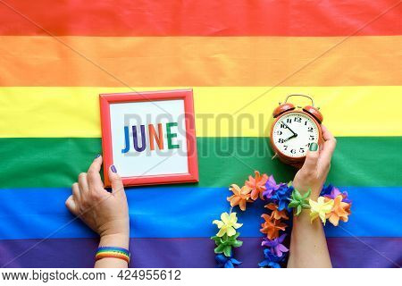 Lgbt Pride Flat Lay With Rainbow Flag. Hands Hold Alarm Clock And Frame With Text Pride Month, June