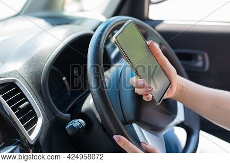 A Faceless Woman Uses A Mobile Phone While Driving A Car. The Girl Uses The Navigation In The Smartp