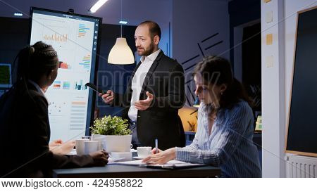Focused Man Leader Explaining Management Project Using Monitor Working In Company Meeting Office Roo