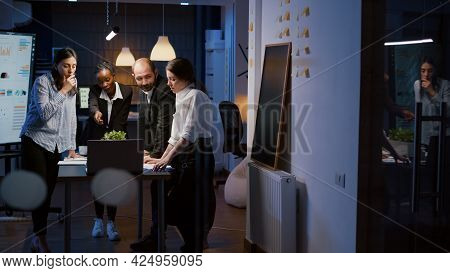 Multi Ethnic Businesspeople Analyzing Management Presentation Using Laptop Computer Overworking In O