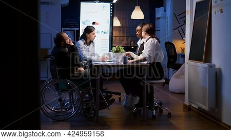 Overworked Disabled Businessman In Wheelchair Is Ignored While Working In Company Business Office Me