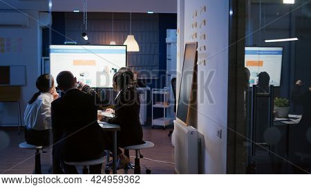 Focused Businessman Presenting Company Solution Using Presentation Monitor Working Overtime In Offic