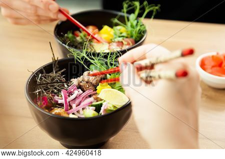 Man And Woman Eating Poke Salad With Chopsticks. Dab Tuna Salad In A Bowl. People In The Restaurant