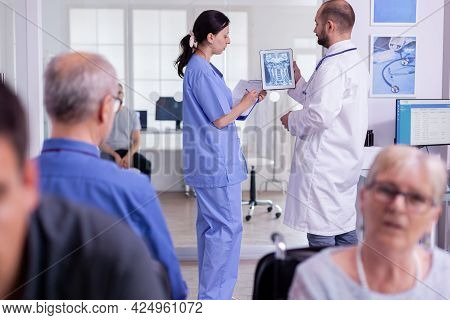Specialist Doctor Examining Radiography With Hopistal Nurse Writing Test Result On Clipboard. Medica