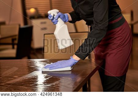 Restaurant Worker Washing A Sprayed Table With Cloth