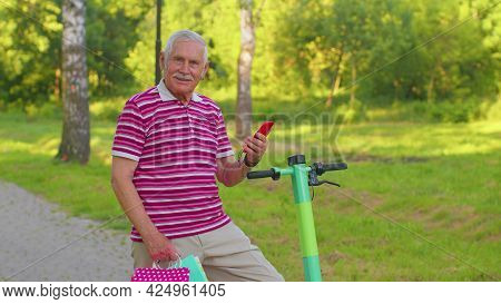 Caucasian Old Senior Grandfather Man Leaning On Electric Scooter After Shopping With Colorful Bags.