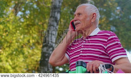 Elderly Old Stylish Grandfather Man Leaning On Electric Scooter After Shopping With Colorful Bags. S