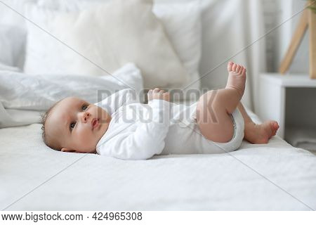 A Charming Boy In A White Sunny Bedroom Plays Alone, Lying On The Bed. A Beautiful Newborn Baby With