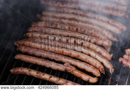 Close Up Cooking Meat Sausages On Grill, Smoking And Broiling Them, High Angle View