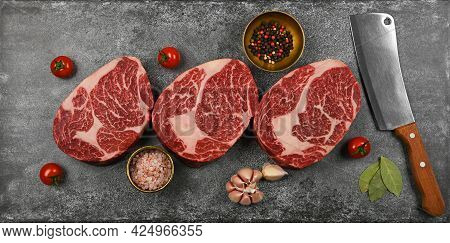Close Up Three Aged Prime Marbled Raw Ribeye Beef Steaks With Cleaver Knife And Spices, Over Stone T