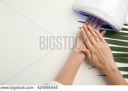Woman Using Ultraviolet Lamp To Dry Gel Nail Polish On White Background, Top View. Space For Text