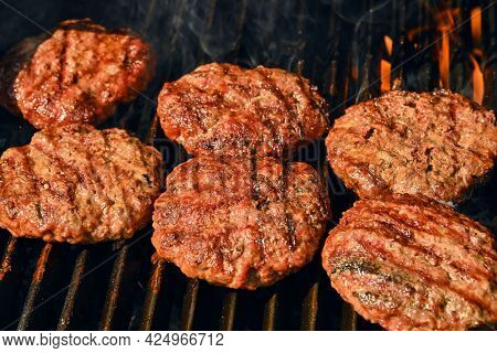 Close Up Searing And Smoking Beef Or Pork Meat Barbecue Burgers For Hamburger On Bbq Fire Flame Gril
