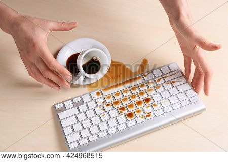 Woman With Coffee Spilled Over Computer Keyboard At Wooden Table, Above View