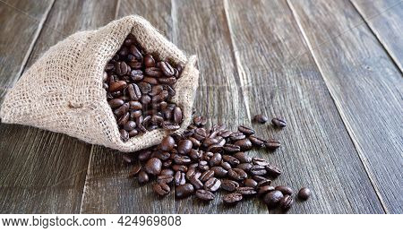 Coffee Beans Scattered From The Sackcloth Bag Against The Wood Background. Sack Bag Full Of Roasted