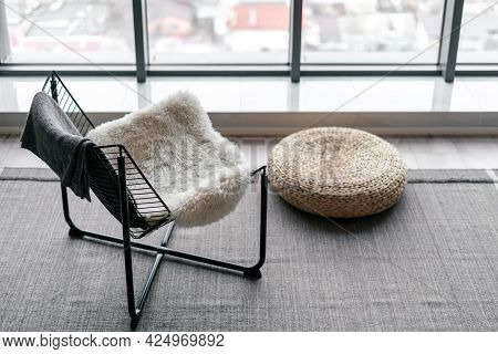 Metal Chair Decorated With Fur Pad Nearby Straw Ottoman On Gray Carpet Against Large Window In Minim