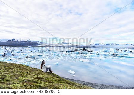 Iceland travel tourist enjoying view of nature landscape Jokulsarlon glacial lagoon glacier lake on Iceland. Woman outdoors by tourist destination landmark attraction. Vatnajokull National Park