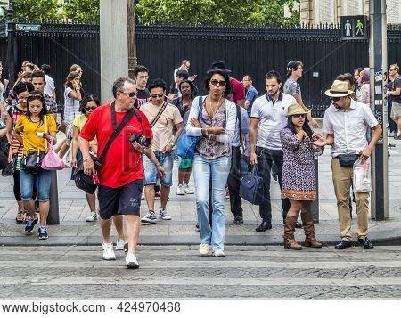 Paris, France - June 12, 2015: People Cross The Street At A Fraffic Light For Pedestrians At A Cross