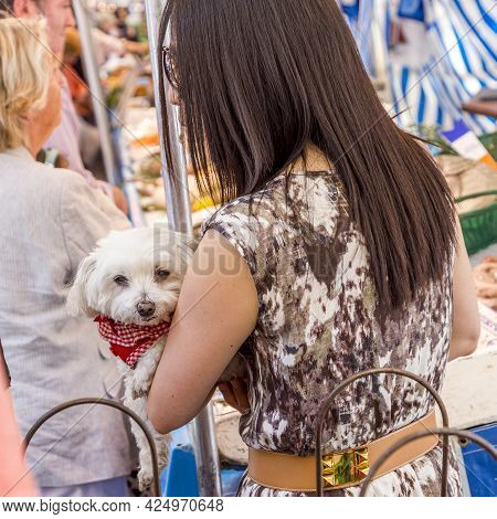 Paris, France - June 13, 2015: Woman Carries Her Small Dog At Her Arm At The  Farmers Market In Chai