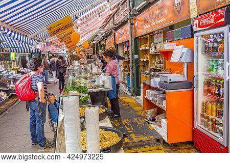 Vienna, Austria - April 28, 2015:  People Enjoy The Naschmarket In Vienna. Since The 16th Century Pe