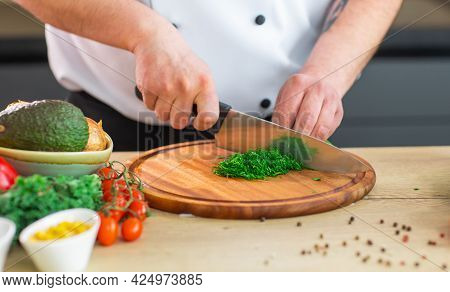 Young Chef Is Cutting Herbs And Parsley In A Modern Kitchen. The Man Prepares Food At Home. Cooking