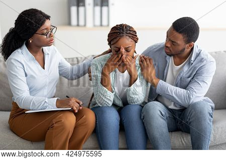 Young Black Woman Crying At Therapists Office, Affectionate Husband Supporting Her With Professional