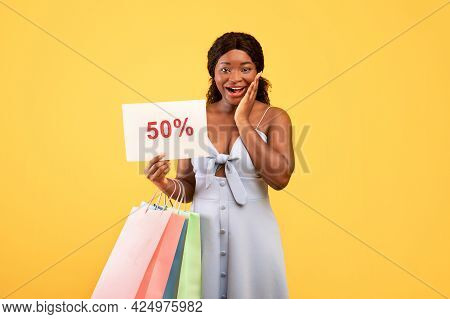 Huge Summer Sales. Excited Young African American Woman Holding Shopping Bags And Fifty Percent Off