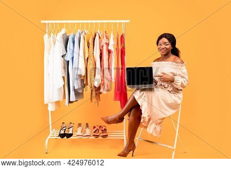 Beautiful Black Woman Sitting Near Clothes Rack With Laptop, Pointing At Empty Screen Over Orange Ba