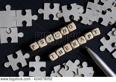 The Word Psychotherapy, Made Up Of Cubes, And Silver Fountain Pen Lie Among The Puzzles On A Dark Ba