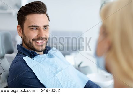 Relaxed Handsome Man Smiling To His Female Dentist