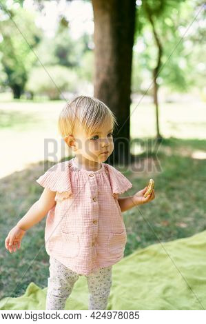 Little Girl With A Pancake In Her Hand Stands On A Blanket On A Green Lawn