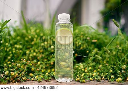 Bottle Of Water With Lemon Stands On A Green Lawn Among Wildflowers