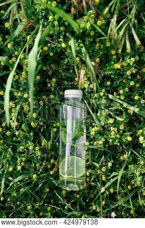 Bottle Of Water Lies On The Green Tall Grass Among Yellow Wildflowers