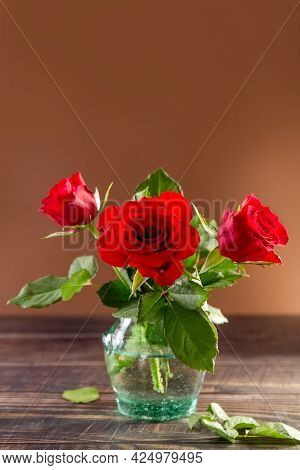 A Bouquet Of Red Roses In A Glass Transparent Vase. Brown Background. Postcard. Poster. High Quality