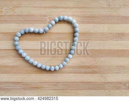 Aquamarine Beads Strand In A Heart Shape On Wood Background. Concept Of Love, Kindness And Valentine