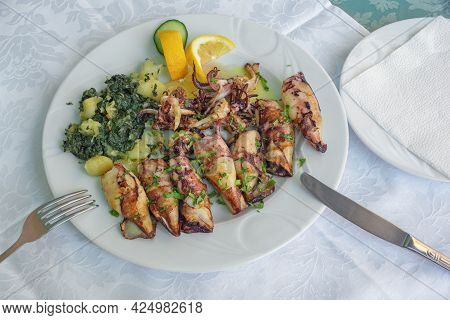 Balkan Cuisine. Dish With Grilled Squids With Chard Leaves ( Blitva ) And Potatoes
