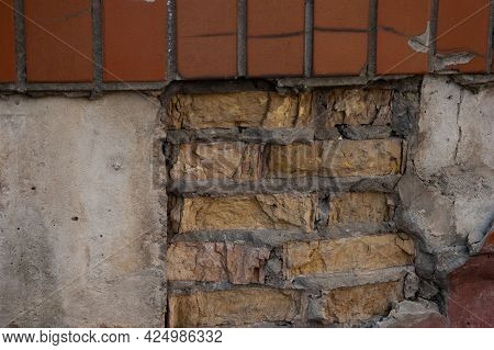 Rough Rimmed Wall With Concrete, Bricks And Brown Tiles
