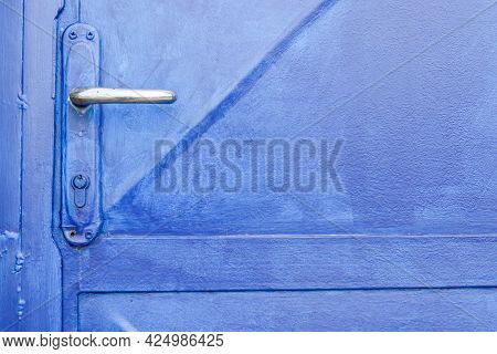 A Close-up Of A Beautiful Blue Artistic Door. The Silver Door Handle Is Set Parallel And At Angles T