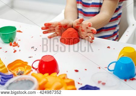 A Child's Hands Play With Bright Kinetic Sand On A White Table. An Educational Game Of Kinetic Sand