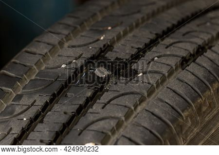 Deep Embedded Of Screw Nail On The Tire. Screw Puncturing Tire. Tire Tread Nail. Replacing The Tires