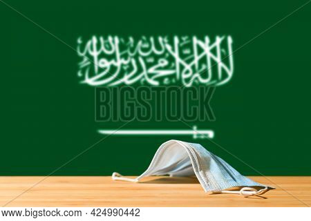 A Medical Mask Lies On The Table Against The Background Of The Flag Of Saudi Arabia. The Concept Of